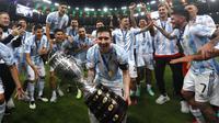 Penyerang  Argentina, Lionel Messi merayakan trofi  Copa America 2021 bersama rekannya usai mengalahkan Brasil 1-0 dalam pertandingan final di stadion Maracana, Brasil, Minggu (11/7/2021). Inilah kali pertamanya  Messi mempersembahkan trofi juara bagi Albiceleste. (AP Photo/Bruna Prado)