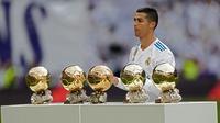 Bintang Real Madrid, Cristiano Ronaldo berpose dengan kelima trofi Ballon d'Or sebelum laga Real Madrid vs Sevilla di Stadion Santiago Bernabeu, Sabtu (9/12). Ronaldo baru saja meraih trofi kelima penghargaan Ballon d'Or 2017 di Paris. (AP/Francisco Seco)