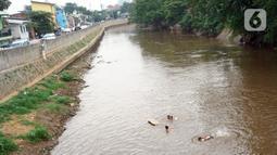 Anak-anak berenang di aliran Sungai Ciliwung, Jatinegara, Jakarta Timur, Sabtu (4/7/2020). Minimnya lahan bermain menyebabkan anak-anak tersebut bermain tidak pada tempatnya, meski dapat membahayakan keselamatan. (Liputan6.com/Immanuel Antonius)