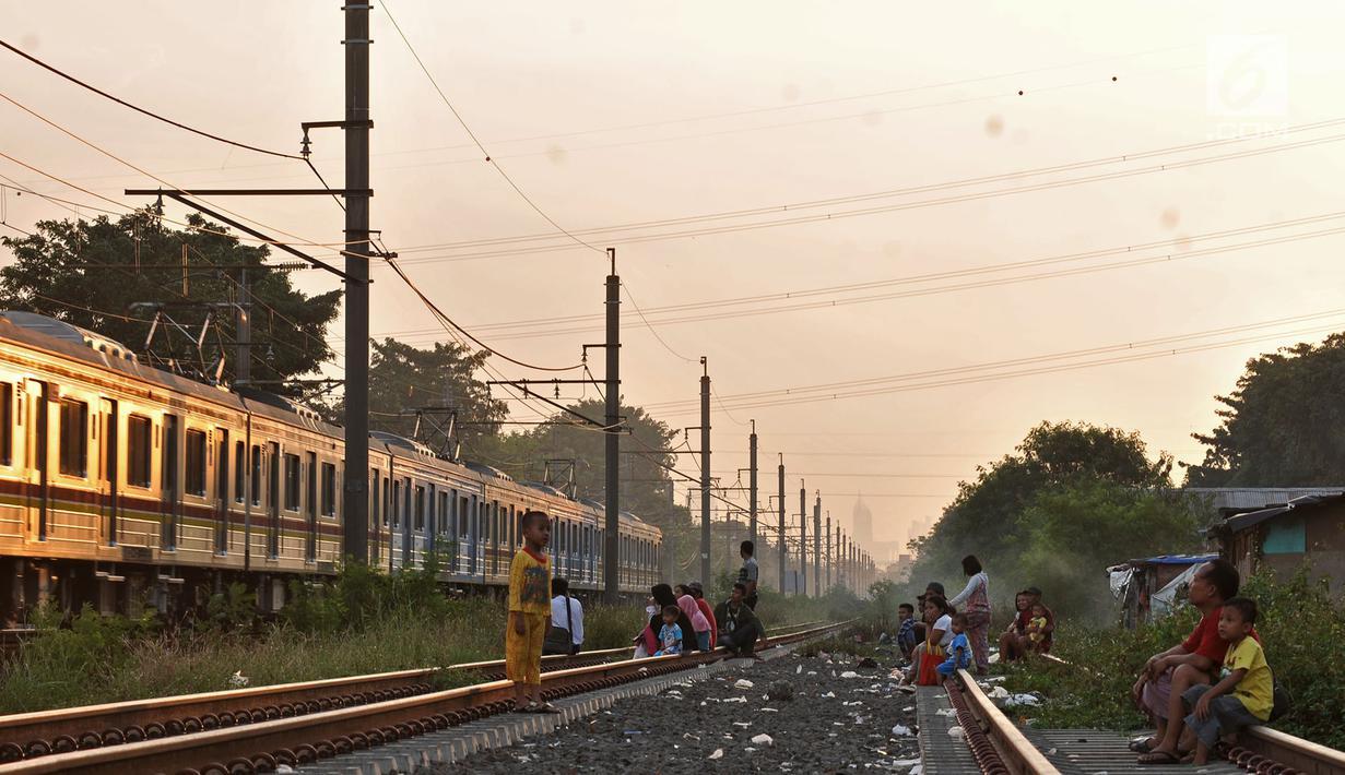 Sejumlah anak-anak didampingi orang tuanya bermain saat menunggu waktu berbuka puasa atau ngabuburit di rel kereta Double Double Track (DDT) di Jakarta, Senin (21/5). (Merdeka.com/Iqbal S Nugroho)