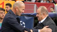 Pelatih Real Madrid Zinedine Zidane (kiri) berbicara dengan Manajer Galatasaray Fatih Terim jelang bertanding pada laga Liga Champions di Istanbul, Turki, Selasa (22/10/2019). Real Madrid mengalahkan Galatasaray lewat gol tunggal Toni Kroos. (AP Photo)
