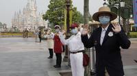Pegawai mengenakan masker saat menyambut wisatawan di taman hiburan Disneyland, Shanghai, China, Senin (11/5/2020). Disneyland Shanghai kembali dibuka setelah tiga bulan ditutup akibat pandemi virus corona COVID-19. (AP Photo/Chen Si)