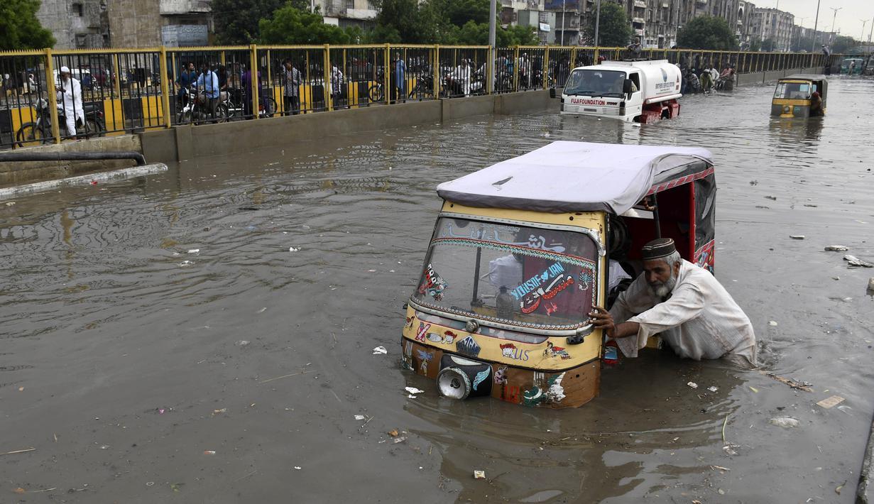 Seorang pengemudi mendorong bajaj saat melewati jalan yang banjir di Karachi, Pakistan, Kamis (23/9/2021). Banjir merendam Karachi setelah diguyur hujan deras. (AP Photo/Fareed Khan)