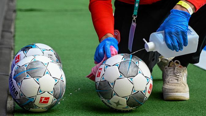 Ball boys wajib membersihkan setiap bola dengan cairan desinfektan sebelum diberikan kepada pemain. (AFP/SASCHA SCHUERMANN)
