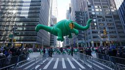 Balon Dino melayang di atas kawasan Sixth Avenue selama Parade Macy's Thanksgiving Day di New York, Kamis (22/11). Balon raksasa berbentuk ikon-ikon kartun terkenal menghiasi gelaran yang digelar untuk ke-92 tersebut. (Don EMMERT / AFP)
