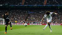 Pemain Paris Saint-Germain, Thomas Meunier mencoba menghentikan tendangan pemain Real Madrid, Marcelo pada leg pertama babak 16 besar Liga Champions di Stadion Santiago Bernabeu, Rabu (14/2). Real Madrid menaklukkan PSG 3-1. (AP/Paul White)