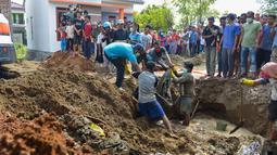 Warga membawa sisa-sisa korban tsunami dan gempa 2004 yang ditemukan di Kajhu, Provinsi Aceh (19/12). Penemuan korban tersebut membuat warga sekitar kaget dan berbondong-bondong menggali tanah di area sekitar. (AFP Photo/Chaideer Mahyuddin)