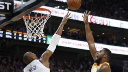 Pemain Utah Jazz,  Derrick Favors (kanan) berusaha menghalau tembakan pemain Warriors, David West pada lanjutan NBA basketball game di Vivint Smart Home Arena, Salt Lake City, (30/1/2018). Utah menang 129-99. (AP/Rick Bowmer)