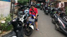 Warga parkir di sekitar Jalan Kebon Pala II, Jakarta, Selasa (25/2/2020). Banjir yang merendam kawasan tersebut menyebabkan warga mengungsikan kendaraannya ke tempat yang lebih tinggi. (Liputan6.com/Immanuel Antonius)