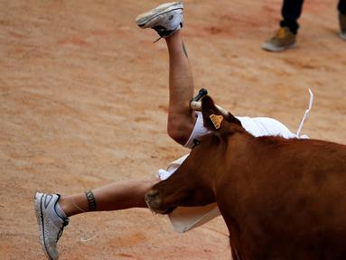 Seorang peserta festival ditanduk Banteng saat berlari pada ajang San Fermin festival di Pamplona, spanyol, (12/7/2016). (REUTERS/Susana Vera)