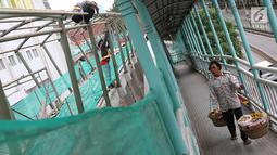 Seorang pedagang melihat pembangunan JPO Pasar Rumput di Jakarta, Selasa (15/1). Pembangunan jembatan di bangunan pasar yang terintegrasi dengan rusun tersebut dibuat untuk memudahkan mobilitas warga. (Liputan6.com/Immanuel Antonius)