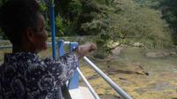 Petugas pintu air menunjuk lokasi penemuan bayi di tepi Sungai Kalisari, Malang, Jawa Timur (Liputan6.com/Zainul Arifin)