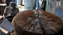 Pengrajin menghaluskan drum saat membuat beduk di kawasan Tanah Abang, Jakarta, Senin (14/5). Beduk biasa dijual dengan kisaran harga Rp 150 ribu hingga Rp 1,5 juta. (Merdeka.com/Iqbal Nugroho)