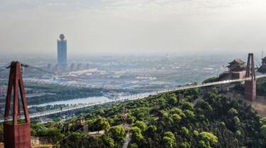 Foto pada 4 Mei 2019 memperlihatkan pemandangan di atas udara atau Skywalk dari jembatan berlantai kaca di Huaxi Adventure Park, Provinsi Jiangsu timur China. Jembatan kaca setinggi 518 meter ini menjadi tujuan wisata favorit di China. (Photo by STR / AFP)