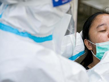 Petugas medis melakukan swab antigen terhadap pengungsi banjir di Universitas Borobudur, Cipinang Melayu, Jakarta, Minggu (21/2/2021). Pengungsi diwajibkan menjalani swab antigen untuk mencegah penyebaran COVID-19. (Liputan6.com/Faizal Fanani)