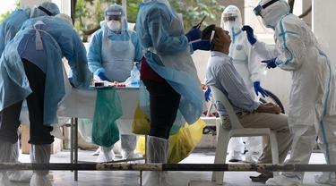 Staf kementerian kesehatan mengumpulkan sampel untuk pengujian virus corona dari seorang penduduk di daerah perkotaan di Bandar Utama, pinggiran Kuala Lumpur, Malaysia pada hari Kamis, 22 Oktober.