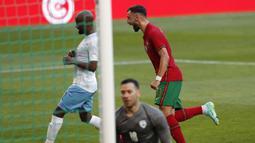 Gelandang Portugal, Bruno Fernandes (kanan) melakukan selebrasi usai mencetak gol pertama Portugal ke gawang Israel dalam laga uji coba menjelang Euro 2020 di Jose Alvalade Stadium, Lisbon, Rabu (9/6/2021). Portugal menang 4-0 atas Israel. (AP/Armando Franca)