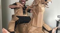 """David Marriott mengunggangi kuda kertasnya """"Russell"""" di kamar hotelnya di Brisbane, Australia, 1 April 2021. Saat berada dalam kamar hotel untuk karantina, direktur seni di iklan TV itu bosan dan mulai membuat pakaian koboi dari kantong kertas makanannya yang dikirimkan. (David Marriott via AP)"""