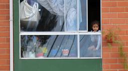 Orang-orang menggantungkan kain merah di rumah mereka untuk meminta bantuan makanan selama lockdown di kotamadya Soacha, dekat Bogota, 4 April 2020. Presiden Kolombia Ivan Duque menetapkan lockdown dari 24 Maret hingga 13 April sebagai langkah mencegah penyebaran virus corona. (Raul ARBOLEDA/AFP)