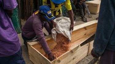 Mr. Jean melempar serbuk gergaji ke dalam peti mati saat bersama timnya membuat peti mati murah di jalan di Antananarivo, Rabu (14/4/2021). Sejak gelombang kedua Covid-19 di Madagaskar, yang menyebabkan jumlah kematian meningkat di ibu kota, permintaan peti mati juga meningkat pesat. (RIJASOLO/AFP)