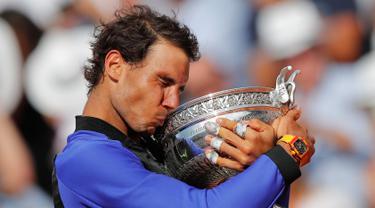 Petenis Spanyol, Rafael Nadal mencium trofinya setelah mengalahkan Stan Wawrinka pada final Prancis Terbuka di Roland Garros, Minggu (11/6). Nadal unggul dengan skor 6-2, 6-3, 6-1 untuk meraih gelar kesepuluh atau La Decima. (AP Photo/Christophe Ena)