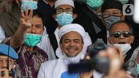 Rizieq Shihab (tengah) memberi keterangan sesaat sebelum masuk gedung utama Mapolda Metro Jaya, Jakarta, Sabtu (12/12/2020). Rizieq Shihab akan menjalani pemeriksan sebagai tersangka penghasutan dan kerumunan di tengah pandemi Covid-19. (Liputan6.com/Helmi Fithriansyah)