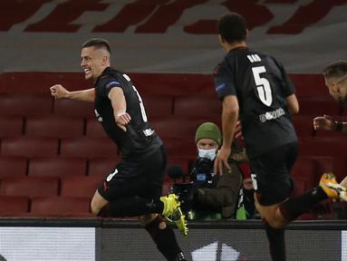 Para pemain Slavia Praha merayakan gol penyeimbang 1-1 ke gawang Arsenal yang dicetak bek Tomas Holes (kiri) dalam laga leg pertama perempatfinal Liga Europa 2020/2021 di Emirates Stadium, London, Kamis (8/4/2021). Slavia Praha bermain imbang 1-1 dengan Arsenal. (AFP/Ian Kington)