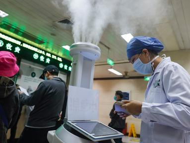 Staf medis menggunakan komputer tablet untuk mengendalikan robot pintar di ruang rawat jalan Rumah Sakit Renmin Universitas Wuhan di Wuhan, 16 Maret 2020. Robot pintar itu mampu melakukan pekerjaan disinfeksi secara otomatis di sejumlah lokasi yang telah ditentukan satu per satu. (Xinhua/Shen Bohan)