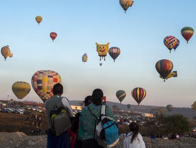 Warga melihat balon udara yang menghiasi langit di Cajititlan, Meksiko, Minggu (7/5).  Festival balon udara ini menjadi tontonan menarik bagi warga sekitar dan wisatawan. (AFP PHOTO / Hector Guerrero)