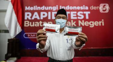 Menko PMK Muhadjir Effendy menunjukkan produk tes cepat Covid-19 di Kantor Kemenko PMK, Jakarta, Kamis (9/7/2020). Pemerintah RI Melalui Kemenko PMK bersama sejumlah kementerian dan lembaga terkait meluncurkan produk tes cepat Covid-19. (Liputan6.com/Faizal Fanani)