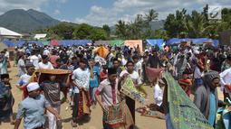 Umat muslim usai melaksanakan salat Jumat di sebuah ladang di dekat tempat penampungan sementara setelah gempa di Pemenang, Lombok (10/8). Jumlah Korban tewas akibat gempa dahsyat 6,9 SR di pulau Lombok melonjak di atas 300 orang. (AFP Photo/Adek Berry)