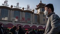 Orang-orang mengenakan masker penutup mulut saat menuju stasiun kereta api Beijing untuk mudik Tahun Baru Imlek pada Selasa (21/1/2020). Virus mirip SARS yang menyebar ke seluruh wilayah China dan mencapai tiga negara Asia ternyata dapat menular dari satu orang ke orang lain. (NICOLAS ASFOURI/AFP)