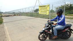 Pengendara sepeda motor berputar arah saat Jalan Perimeter Utara diblokir warga, Rawa Rengas, Kosambi, Tangerang, Banten, Selasa (2/7/2019). Proses hukum akses menuju Bandara Soekarno-Hatta (Soetta) tersebut masih berlangsung di Pengadilan Negeri Tangerang. (merdeka.com/Arie Basuki)