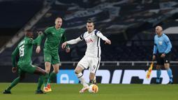 Gelandang Tottenham, Gareth Bale, berebut bola dengan gelandang Ludogorets, Stephane Badji, pada laga lanjutan Grup J Liga Europa di Tottenham Hotspur Stadium, Jumat (27/11/2020) dini hari WIB. Tottenham menang 4-0 atas Ludogorets. (AFP/Ian Kington/pool)