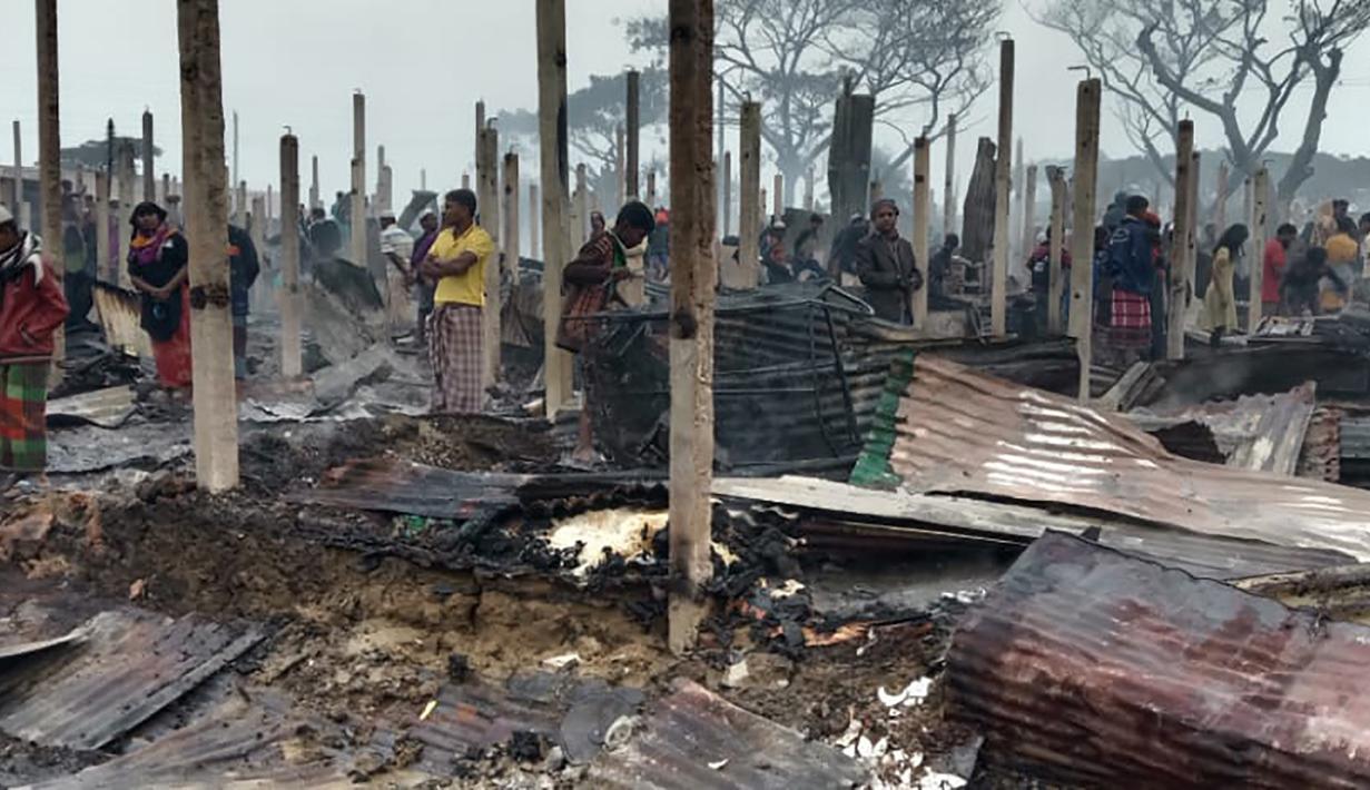 Pengungsi Rohingya berjalan di sisa-sisa yang hangus setelah kebakaran terjadi di Kamp Nayapara di distrik Cox's Bazar, Bangladesh, Kamis (14/1/2021). Ratusan rumah yang menjadi tempat tinggal ribuan pengungsi Rohingya hancur akibat dilalap api. (AP Photo/Mohammed Faisal)