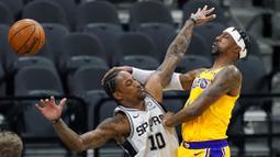 Pebasket Los Angeles Lakers, Kentavious Caldwell-Pope, berebut bola dengan pebasket San Antonio Spurs, DeMar DeRozan, pada laga NBA di AT&T Center, Kamis (31/12/2020). LA Lakers menang dengan skor 121-107. (AP/Eric Gay)