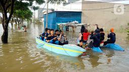 Warga menggunakan perahu karet melintasi banjir yang melanda Perumahan Total Persada, Periuk, Kota Tangerang, Selasa (4/2/2020). Banjir akibat tanggul kali Ledug jebol membuat ratusan rumah di Total Persada terendam banjir hingga mencapai 3,5 meter. (merdeka.com/Arie Basuki)