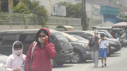 Warga mengenakan masker berjalan setelah letusan Gunung Merapi di Solo (3/3/2020). Hujan abu yang melanda kota Solo membuat Bandara Internasional Adi Soemarmo ditutup. (AFP Photo/Dika)