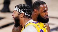 Pebasket Los Angeles Lakers, LeBron James dan Anthony Davis, melakukan selebrasi saat melawan Miami Heat pada gim pertama final NBA di Lake Buena Vista, Kamis (1/10/2020). Lakers menang dengan skor 116-98. (AP Photo/Mark J. Terrill)