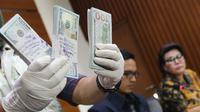 Petugas memperlihatkan uang yang berhasil disita dari pejabat PT PAL terkait dugaan suap pengadaan kapal ke Filipina, Jakarta, Jumat (31/3). KPK menyita 25 ribu dolar AS dan menahan 4 tersangka. (Liputan6.com/Helmi Afandi)