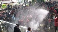 Massa unjuk rasa dihalau polisi dengan semprotan water canon di depan Gedung DPRD Malang. (Merdeka/Darmadi Sasongko)