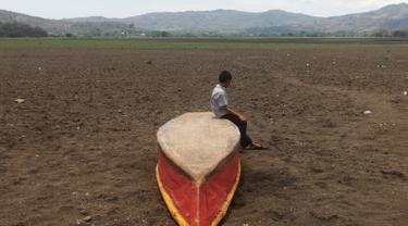 """Seorang anak laki-laki duduk di atas kapal di Danau Atescatempa yang telah mengering, Guatemala, Jumat (5/5). Keringnya Danau Atescatempa disebabkan oleh dampak perubahan iklim di Amerika Tengah yang disebut """"Koridor Kering"""". (AFP PHOTO / Marvin RECINOS)"""