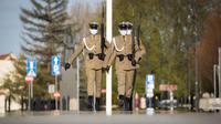 Para tentara yang mengenakan masker melakukan pertukaran sif di Makam Prajurit Tak Dikenal di Warsawa, Polandia (20/4/2020). Pemerintah Polandia telah melonggarkan beberapa kebijakan pembatasan terkait pandemi COVID-19 pada Senin (20/4). (Xinhua/Jaap Arriens)