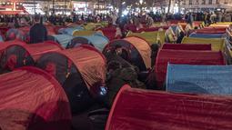 Aktivitas para migran di tenda yang mereka dirikan di Republic square, pusat kota Paris, pada Kamis (25/3/2021). Hampir 400 tenda didirikan di alun-aun tersebut untuk menarik perhatian atas kondisi kehidupan mereka dan menuntut akomodasi. (AP Photo/Rafael Yaghobzadeh)