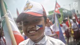 Seorang siswa SD mengenakan atribut bendera negara peserta Asian Games 2018 saat menyambut Kirab Obor di kawasan Jati Padang, Pasar Minggu, Rabu (15/8). Mereka memenuhi jalanan untuk menyaksikan langsung Pawai Obor Asian Games (Liputan6.com/Faizal Fanani)