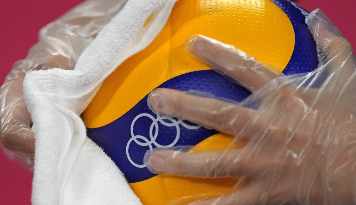 Petugas mengenakan sarung tangan plastik dan kain saat mendisinfeksi bola voli jelang pembukaan pertandingan voli Olimpiade Tokyo 2020 di Ariake Arena, Tokyo, Jepang, Jumat (23/7/2021). Olimpiade Tokyo 2020 digelar dengan penerapan protokol kesehatan ketat. (AP Photo/Frank Augstein)