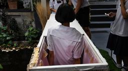 Seorang siswa remaja mencoba masuk ke dalam peti mati di Kid Mai Death Awareness Cafe, Thailand (30/3). Cafe ini menyediakan ruang pameran yang dibangun untuk mendidik masyarakat tentang kematian dan agama Buddha di Bangkok. (AFP/Lillian Suwanrumpha)