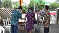 Salah satu jemaah Gereja Katolik Santo Yoseph Palembang dicek suhu tubuh sebelum masuk ke kawasan gereja dalam rangka mengikuti malam Misa Natal 2020 (Liputan6.com / Nefri Inge)