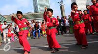 Tiga pendekar cilik memeragakan gerakan pencak silat di Jakarta, Minggu (7/8). Sekitar 1000 pendekar memadati Bundaran HI untuk merayakan Lebaran Pendekar Betawi 2016. (Liputan6.com/Angga