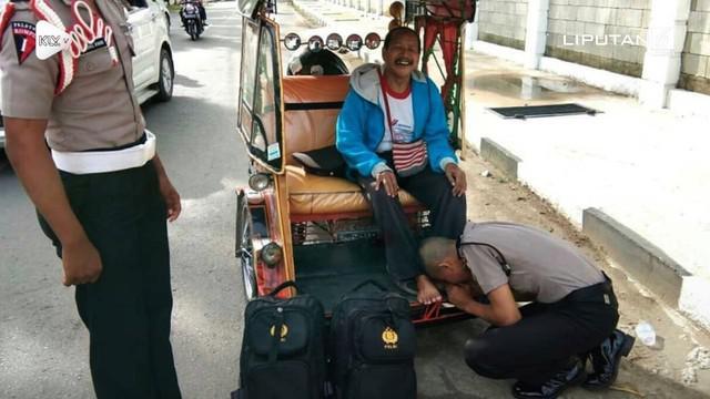 Seorang anak yang jadi polisi mencium kaki ayahnya yang merupakan seorang tukang becak bentor.